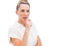 Fokuserad affärskvinna med pennan på mun Fotografering för Bildbyråer