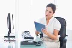 Fokuserad affärskvinna som använder hennes digitala minnestavla på skrivbordet Arkivbild