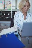 Fokuserad affärskvinna som arbetar på bärbara datorn på kontoret Royaltyfria Bilder