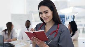 Fokuserad caucasian kvinnlig doktor som gör någon anmärkning i anteckningsboken medan lag av personalen som in talar på bakgrunde stock video