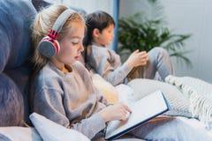 Fokuserad flicka i hörlurar och pysen som använder digitala minnestavlor Royaltyfri Fotografi