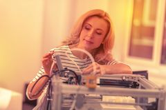 Fokuserad härlig kvinna som ut kontrollerar delarna av en skrivare 3D royaltyfri fotografi