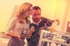 Fokuserad klyftig kvinna som gör sig förtrogen med begreppet av en skrivare 3D royaltyfria foton