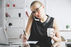 Fokuserad kvinna på telefonen som gör skrivbordsarbete Royaltyfri Fotografi