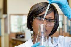Fokuserad kvinnlig forskare med droppglasets Arkivfoto