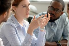 Fokuserad kvinnlig mentorförhandlarelagledare som talar på det olika gruppmötet royaltyfri foto