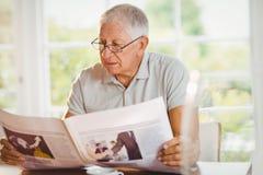 Fokuserad läs- tidning för hög man Arkivbild