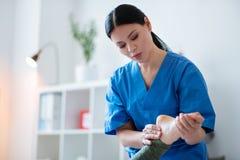 Fokuserad långhårig kvinna i den blåa likformign som gör benmassage arkivbild
