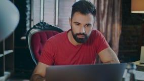 Fokuserad man som arbetar på bärbar datordatoren i hem- arbetsställe Arbete för hem- affär arkivfilmer