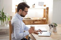 Fokuserad manlig anställd som arbetar på bärbara datorn som dricker kaffe royaltyfri foto