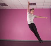 Fokuserad manlig balettdansör som hoppar upp Arkivbild