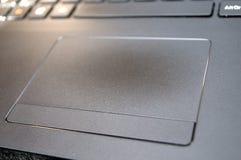 Fokuserad mus som ska tryckas på på den svarta bärbara datorn Royaltyfri Bild