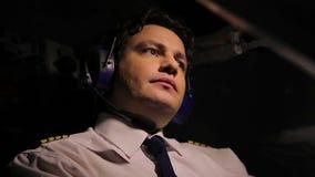 Fokuserad pilot som navigerar trafikflygplanet som ser på himmel Flyg flygtransport lager videofilmer
