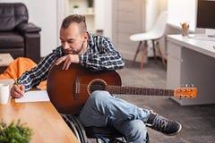 Fokuserad rörelsehindrad man som är förlovad i songwriting Royaltyfri Bild