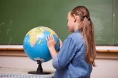 Fokuserad schoolgirl som ser ett jordklot Fotografering för Bildbyråer