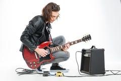 Fokuserad stilig ung gitarrist som spelar den elektriska gitarren med förstärkaren royaltyfria foton