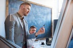 Fokuserad ung affärsman som ger en presentation i ett kontor Royaltyfria Foton