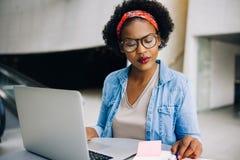 Fokuserad ung afrikansk kvinnlig entreprenör som arbetar på hennes affär royaltyfri fotografi