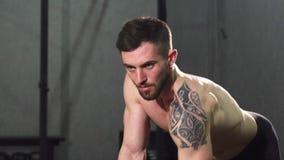Fokuserad ung shirtless manlig idrottsman nen som gör tillbaka genomkörare på idrottshallen arkivfilmer