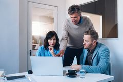 Fokuserade affärskollegor som tillsammans talar, medan genom att använda en bärbar dator Royaltyfria Bilder