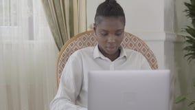 Fokuserade den attraktiva afican amerikanska kvinnan för ståenden att arbeta med hennes upp till dagbärbar dator som sitter på få arkivfilmer