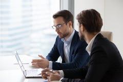 Fokuserade manliga chefer som diskuterar projektet som är upptaget på bärbara datorn royaltyfri foto