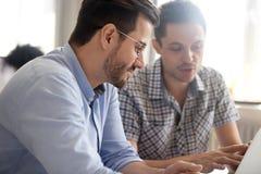 Fokuserade manliga kollegor arbetar tillsammans genom att använda bärbara datorn som diskuterar på arkivfoto