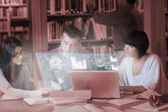 Fokuserade mogna studenter som tillsammans arbetar på digital manöverenhet Royaltyfri Fotografi
