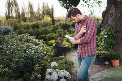 Fokuserade trädgårdsmästaredanandeanmärkningar i anteckningsbok, medan kontrollera växter i trädgård Arkivfoto