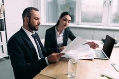 fokuserat affärsfolk som arbetar samman med dokument på arbetsplatsen med bärbara datorn royaltyfri foto