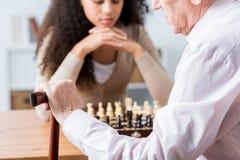 Fokuserat folk som spelar schack royaltyfri fotografi