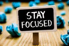 Fokuserat handskrifttextstag Begreppsbetydelsen är den uppmärksamma koncentraten prioriterar uppgiften undviker den skrynkliga fö royaltyfri bild