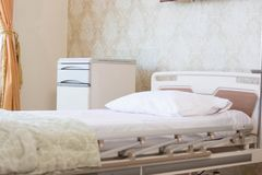 Fokuserat inomhus lyxigt tomt sjukhusrum med bekväm säng med kudden i vit satäng och elektrisk service på dagljus royaltyfri bild