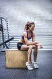 Fokuserat muskulöst kvinnasammanträde på en ask arkivfoton