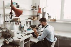 Fokuserat på hans jobb Sidosikt av en manlig juvelerare som ser cirkeln till och med mikroskopet i ett seminarium royaltyfri foto