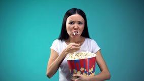 Fokuserat p? filmkvinnan som slukar popcorn fr?n den stora pappers- koppen, sjukligt ?ta arkivbild