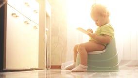 Fokuserat roligt behandla som ett barn brukssmartphonen, medan sitta på pottan stock video