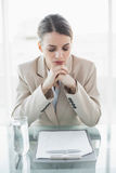 Fokuserat ungt affärskvinnasammanträde på hennes skrivbord som läser henne anmärkningar Arkivbilder