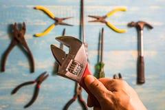 Fokusfläckflyttning skiftnyckeln i hand Hantverkarehjälpmedel på en trätabell Arkivfoto