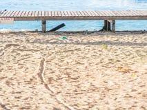 Fokussieren Sie am hölzernen Fußweg mit undeutlichem sandigem Strand Lizenzfreie Stockbilder