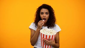 Fokussierte afro-amerikanische Frau, die Popcorn isst und interessante Show aufpasst lizenzfreies stockfoto