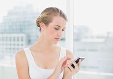 Fokussierte blonde Frauenversenden von sms-nachrichten Lizenzfreie Stockbilder