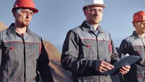 Fokussierte erfahrene Gruppe der industriellen m?nnlichen Arbeitskraft, die auf Baustelle am mittleren Schuss des Sonnenuntergang stock footage