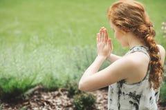 Fokussierte Frau mit den verbindenden Händen Lizenzfreie Stockfotos