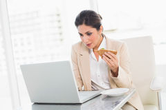 Fokussierte Geschäftsfrau, die das Mittagessen isst, wie sie arbeitet Lizenzfreie Stockfotografie