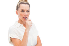 Fokussierte Geschäftsfrau mit Stift auf Mund Stockbild