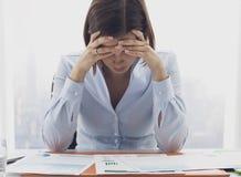 Fokussierte Gesch?ftsfrau, die Finanzberichte und das Denken ?berpr?ft stockbild