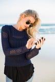 Fokussierte herrliche blonde Versenden von SMS-Nachrichten Stockfotografie