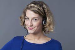 Fokussierte junge Frau, die Kopfhörer für antwortenden Telefonanruf verwendet Lizenzfreies Stockfoto