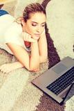 Fokussierte junge Frau, die Laptop beim Lügen auf Boden verwendet lizenzfreies stockfoto
